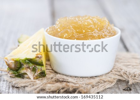 Bowl with Pineapple Jam and fresh fruits on wooden background - stock photo