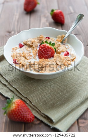 Bowl with rice flakes and strawberry for nourishing breakfast - stock photo