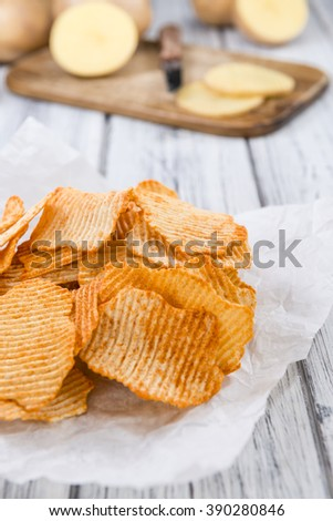 Bowl with rippled Potato Chips (selective focus) on wooden background - stock photo