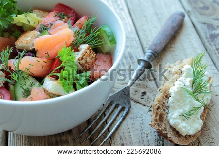 Bowl with salad - smoked salmon, vegetables and brown bread with cheese and fennel - stock photo