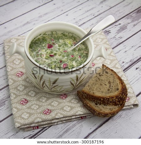 Bowl with summer cold soup (okroshka) and rye bread on wooden background
