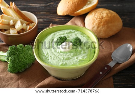 Bowl with tasty broccoli soup on table