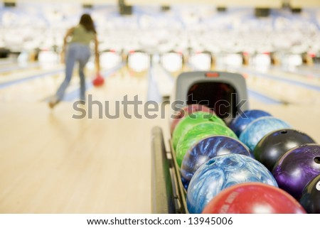 Bowling ball machine with woman bowling in the background - stock photo