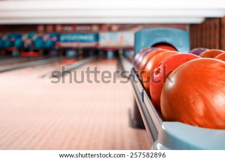 Bowling game. Closeup of bowling balls lying on bowling alley - stock photo