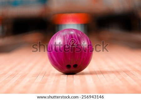 Bowling in details. Closeup of lilac bowling ball lying on bowling alley - stock photo