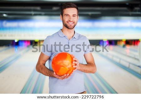 Bowling master. Cheerful young man holding a bowling ball and smiling at camera while standing against bowling alleys - stock photo