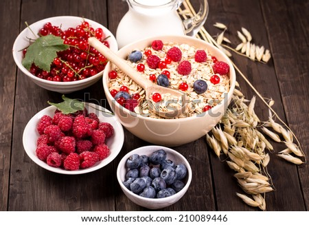 Bowls of oat flakes cereal and various berries.Raspberry, blueberry and redcurrant. - stock photo