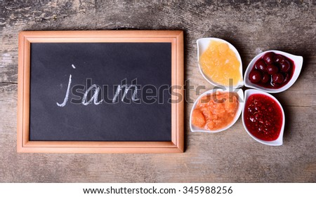 Bowls of tasty jam on wooden background & blackboard with text - stock photo