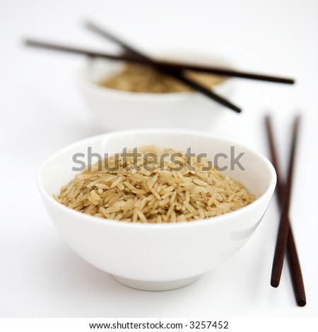 Bowls of uncooked brown rice & chopsticks - shallow dof - stock photo