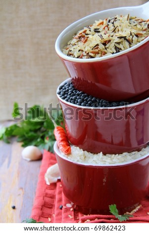 Bowls of uncooked rice and chili peppers Asian Still Life - stock photo