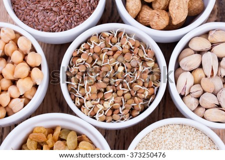 Bowls of various legumes and seeds. Lentils, sesame seeds, pistachio nuts, flaxseed, raisins, peanuts, chickpeas.   - stock photo