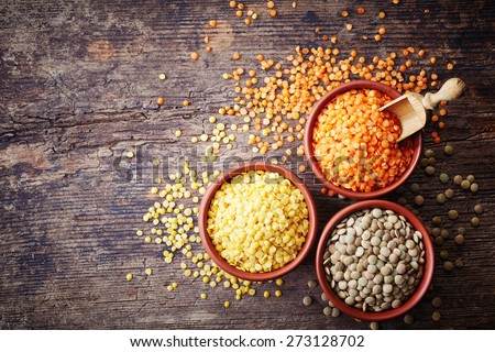 Bowls of various legumes (red turkish lentils, yellow indian lentils, canadian lentils) on wooden background - stock photo