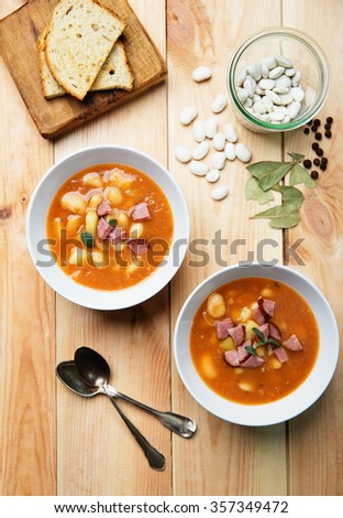 bowls of white bean soup on rustic wooden background - stock photo