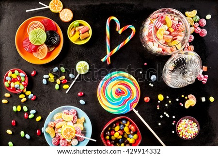 Bowls of yummy jelly beans and licorice rolls besides large sucker, jar filled with hard candies and small lollipops against a black background - stock photo