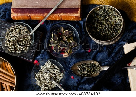 Bowls with different types of tea.  Cup with green chainese  tea and teapot on grey wooden background