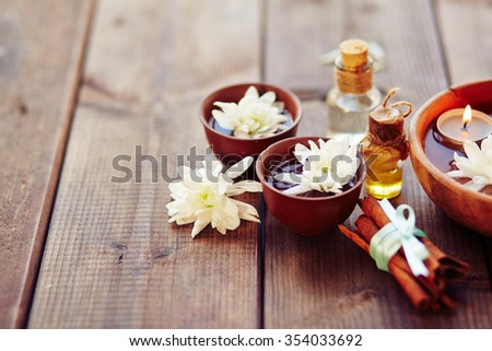 Bowls with flowers, bunch of cinnamon and aromatic oils in spa salon