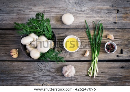 Bowls with mushrooms champignons, herbs and spices on the old wooden background, rustic style, top view, tinted - stock photo