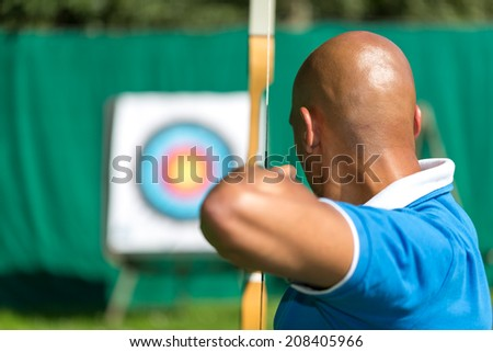Bowman or archer aiming at target with bow and arrow - stock photo