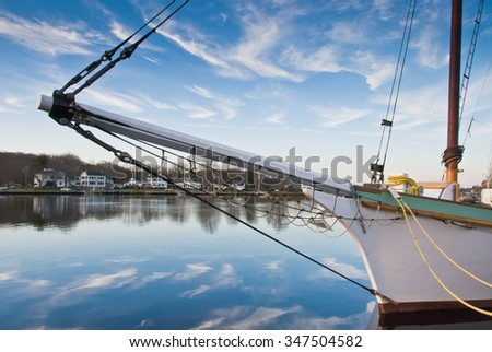 Bowsprit and Blue Sky / Wooden sailing schooner's bowsprit in foreground quayside. Brilliant blue sky with wisps of white clouds is mirrored  in still water.  Colonial homes line the opposite bank.   - stock photo