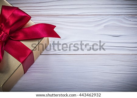 Box-container with present tied bow on wooden board holidays concept. - stock photo