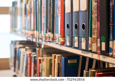 Box file folders on a bookshelf in a library