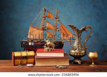 Box for jewelry, books and miniature sailing ship on the table - stock photo