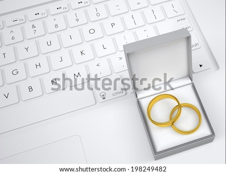 Box for jewelry with two gold rings on the keyboard. View from above - stock photo
