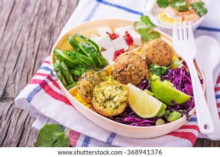 Box Lunch for lunch with cous cous, falafel chick peas, red cabbage salad, slices of cucumber, feta cheese and salad hummus in a white plastic container with a fork and spoon cilantro. selective Focus