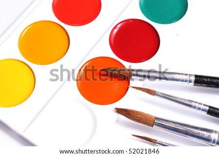 Box of children's water colour paints with brushes on white background