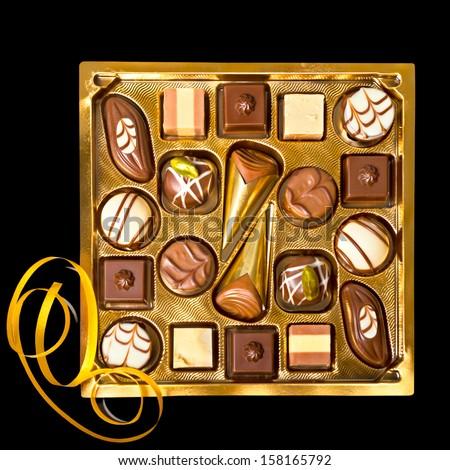 Box of chocolate pralines on black background - stock photo