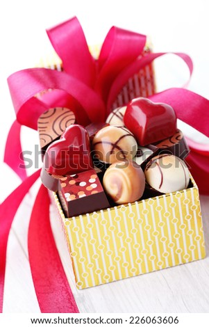 box of chocolates with red ribbon - sweet food - stock photo