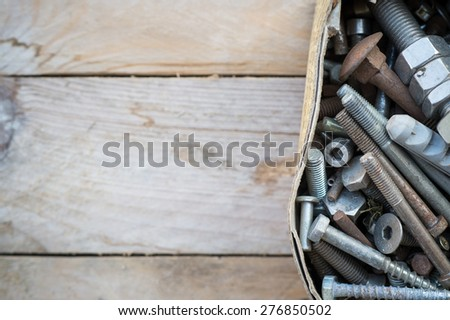 Box of old rusty metal screws on wooden background