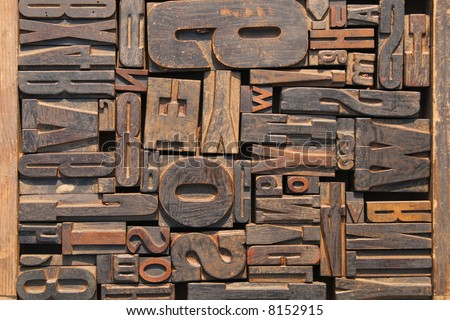Box of old wooden printing blocks with different sized letters - stock photo