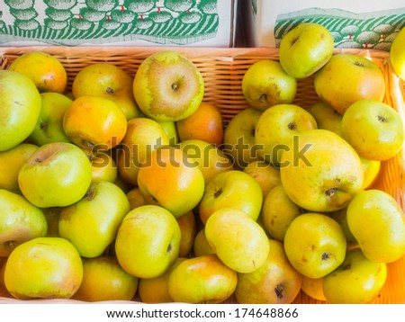 Box of organic Newtown Pippin apples for sale at local farmers market. Newtown Pippin is typically light green, sometimes with a yellow tinge. - stock photo