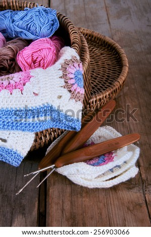 Box of pink and blue yarn and granny square blanket with crochet hooks - stock photo