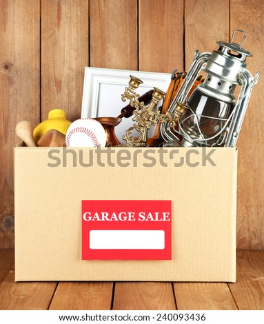 Box of unwanted stuff ready for a garage sale on wooden background - stock photo