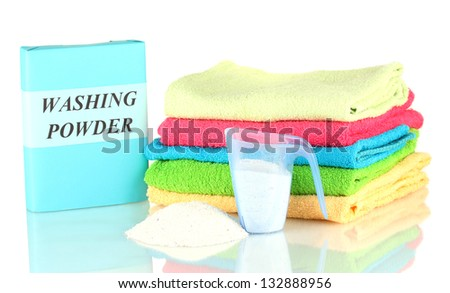 Box of washing powder with blue measuring cup and towels, isolated on white - stock photo