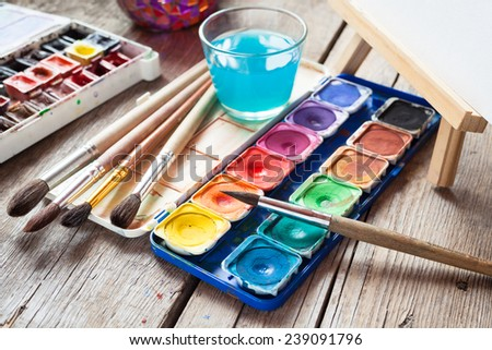 Box of watercolor paints, art brushes, glass of water and easel with canvas or paper on old wooden table. - stock photo