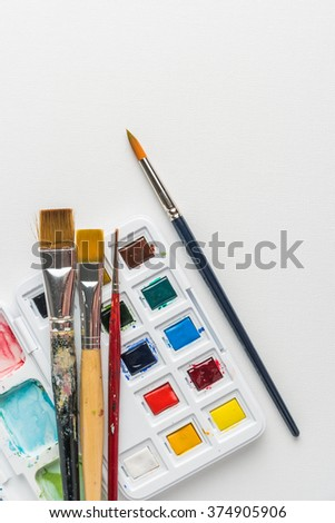 Box of watercolor paints, art brushes on canvas. Top view with copy space. - stock photo