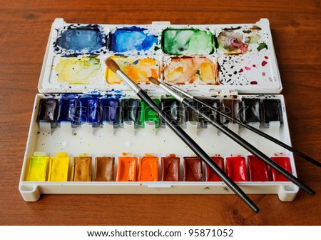 box of watercolors on wooden desk - stock photo
