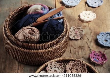 Box of yarn and handmade crocheted flowers - stock photo