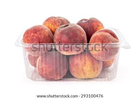 Box or punnet of fresh ripe organic peaches isolated on white background - stock photo