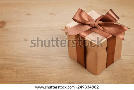 Box with a gift and a bow on the board - stock photo