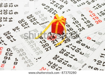 Box with a gift on calendar sheet - stock photo