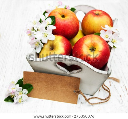 box with apples  and apple tree blossoms and empty tag on a  wooden table
