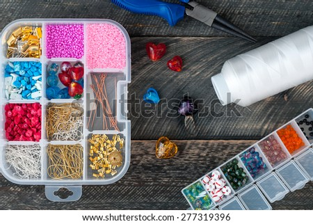Box with beads, spool of thread, plier and glass hearts to create hand made jewelry on old wooden background. Handmade accessories. Top view - stock photo