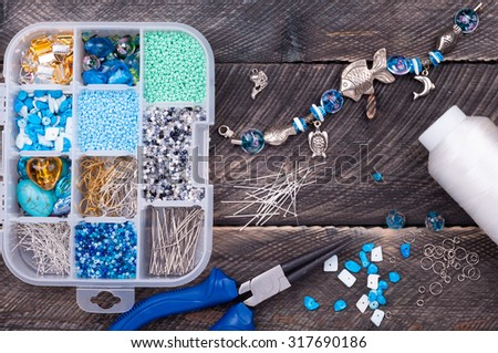 Box with beads, spool of thread, plier and glass hearts to create hand made jewelry on old wooden background. Making bracelet. Handmade accessories. Top view - stock photo