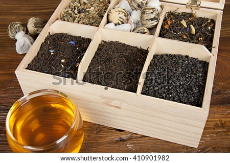 box with different kind of tea and glass of tea - stock photo