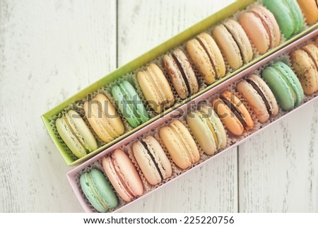 box with macaroons on wooden background - stock photo