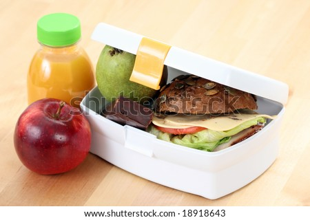 box with sandwich fruits and chocolate and bottle of juice - stock photo